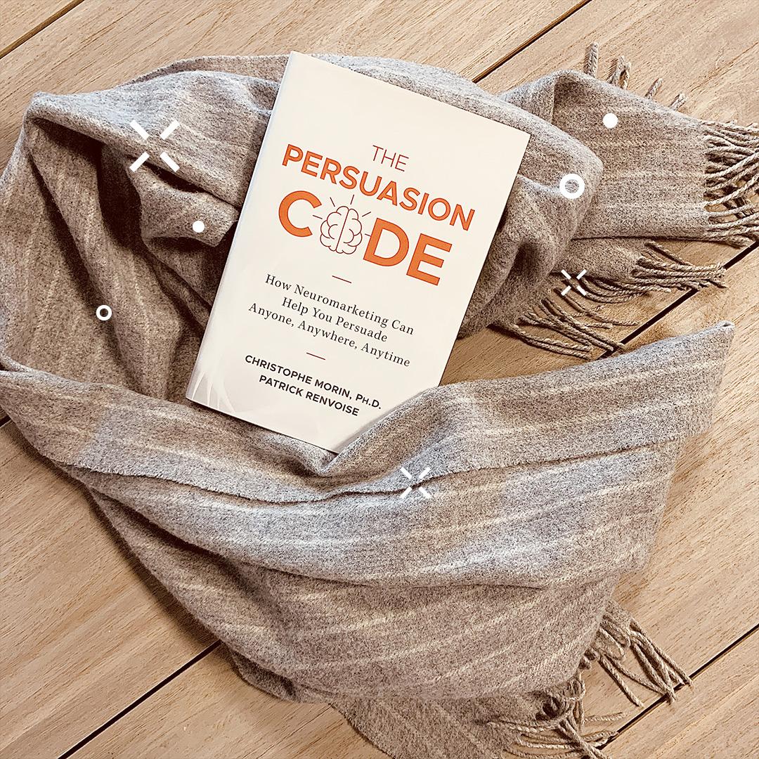 Photographie du livre The Persuasion Code sur une écharpe