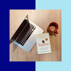 Le livre Sapiens, un ordinateur et un café