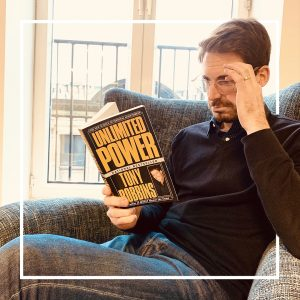 Une homme lit Unlimited Power de Tony Robbins