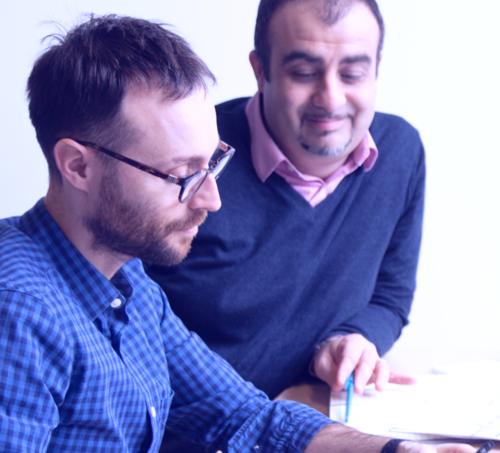 Photographie de deux hommes réfléchissant au dessus d'une feuille prise pendant un Design Sprint