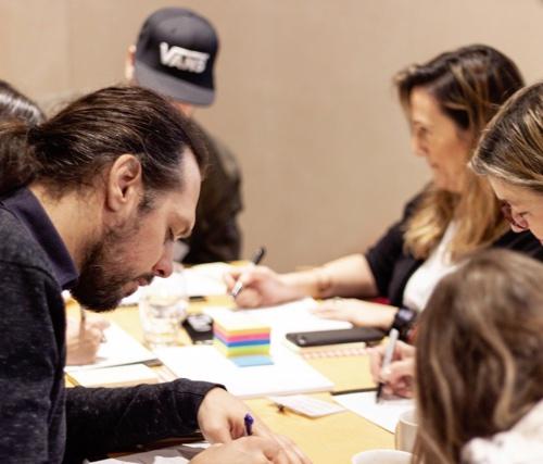 Photographie de plusieurs personnes en train de réaliser un exercice de Design Thinking sur une table