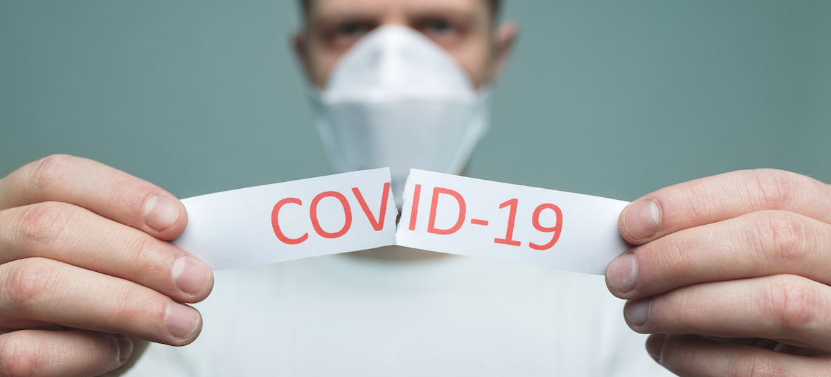 Un homme avec un masque qui déchire un papier contenant le mot COVID-19